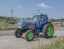 农业拖拉机的竞争在绿色草甸 bjorn 免版税库存照片