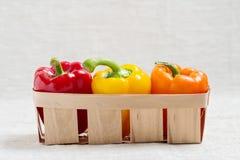 农业新鲜市场产品蔬菜 在红色篮子的三个甜椒,黄色 库存图片