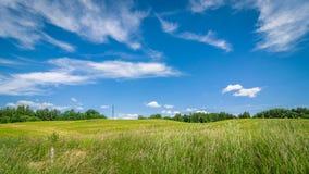 农业横向夏天 一个多小山领域在蓝色多云天空下 免版税库存图片
