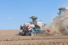 农业种植玉米的春天庄稼大农场主和耙 免版税库存图片