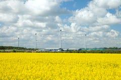 农业飞机棚和风轮机在油菜籽调遣 库存图片