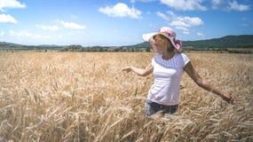 农业:草帽的一个女孩检查与成熟耳朵的一块麦田 晴朗的天气,蓝天,云彩 免版税库存照片