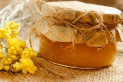 农业 开户用与黄色干燥花的蜂蜜在粗麻布 侧视图 免版税图库摄影