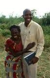 农厂工人拥抱一名官员,乌干达。 免版税库存照片