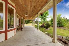 农厂房子外部 与摇椅的入口门廊 库存图片