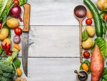 农厂新鲜蔬菜的可口分类与刀子和匙子的在白色木背景,顶视图 素食成份fo 免版税库存图片
