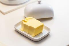 农厂黄油的帕特在一个陶瓷奶油碟的 库存照片