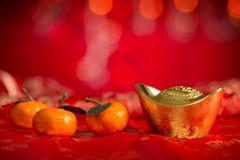 农历新年装饰金锭和橘子 免版税库存照片