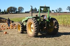 农场工人在萨利姆,俄勒冈附近卸载从拖拉机的南瓜 免版税库存图片