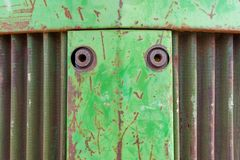农场设备拖拉机的前面鼻子 金属与铁锈、弯曲的金属出气孔和绿色切削的油漆的背景照片 免版税库存照片