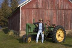 农夫他的摆在拖拉机 免版税库存照片