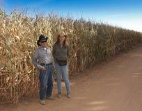 农夫和他的女儿支持玉米田 库存照片