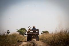 农夫在坚硬工作回去在家在灰色天空以后 免版税库存照片