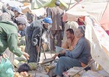 农夫在摩洛哥坐卖他的产物的等待在索维拉之外的每周巴巴里人开放的市场上 妇女很少出席一个标记 库存照片