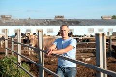 农夫在有奶牛的农场工作 免版税图库摄影