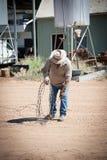 农夫在物产滚动铁丝网的长度与皮手套的 免版税库存照片