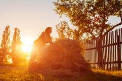 农夫妇女会集与干草叉的干草在日落在乡下 坚苦工作在村庄 免版税库存图片