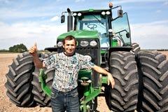 农夫姿态好的显示的拖拉机 免版税库存照片