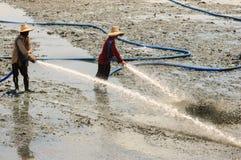 农夫用高压水清洗虾农场 免版税图库摄影