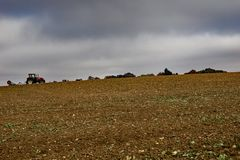 农夫耕种在小山的一个领域在更低的Sheering艾塞克斯 晚秋天和雨期望 免版税库存照片