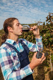 年轻农夫饮用的酒 库存图片