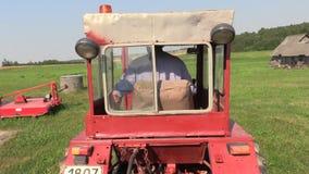 农夫驱动一台老红色拖拉机通过草甸 股票视频