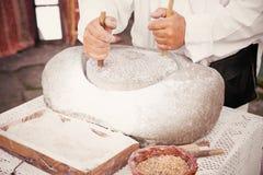 农夫驾驶一个老手磨房由麦子做面粉 免版税库存照片