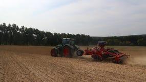 农机-拖拉机、播种机、喷雾器和耕地机在领域运转 库存照片