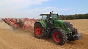 农机-拖拉机、播种机、喷雾器和耕地机在领域运转 库存图片