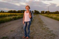 农村农场马路的可爱的白肤金发的妇女 免版税库存照片