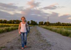 农村农场马路的可爱的白肤金发的妇女 免版税库存图片