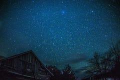农村原木小屋谷仓在与星和银河的晚上 免版税图库摄影