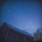 农村原木小屋谷仓在与星和银河的晚上 免版税库存照片