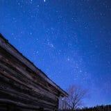 农村原木小屋谷仓在与星和银河的晚上 库存照片