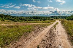 农村土路在一个多小山区域在蓝色多云天空下 图库摄影