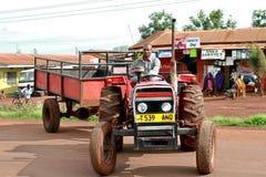 从农村坦桑尼亚的非洲农夫,驾驶牵引车拖车 库存照片
