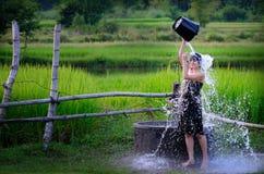 农村女孩洗从传统地水的澡在 免版税库存图片