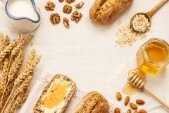 农村或国家早餐-小圆面包,蜂蜜瓶子,牛奶 库存照片