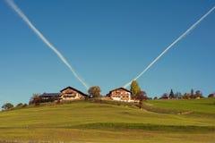 农村房子和一个农场反对飞机在清楚的蓝天追踪 免版税库存照片