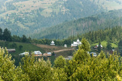 农村房子和一个教会树木丛生的山背景的  免版税图库摄影