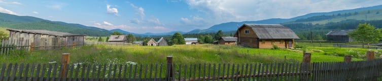 农村房子在庭院里长满与在一个非常美丽的山平原的草 免版税库存照片