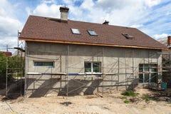农村房子的建筑或修理有绝缘材料的,房檐,窗口,烟囱,屋顶,定象门面,涂灰泥墙壁 免版税图库摄影