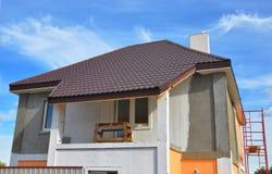 农村房子的建筑或修理有阳台的,房檐,窗口,烟囱,屋顶,定象门面,绝缘材料,涂灰泥 免版税库存图片