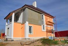农村房子的建筑或修理有balcon、房檐、窗口、烟囱、屋顶、定象门面、绝缘材料和绘画的 库存照片