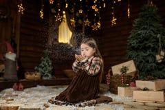农村样式打扮了女孩坐地板吹从她的做愿望的棕榈的雪 圣诞节童话魔术 节假日概念 库存照片