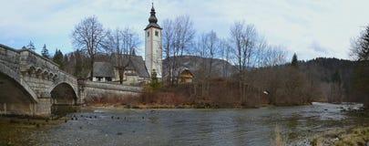 农村桥梁、教会和河全景 库存照片