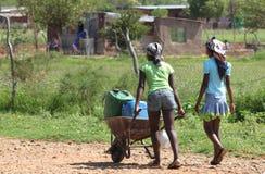 农村生活-用车运送水家的村庄女孩 免版税库存照片
