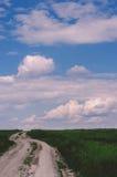 农村的横向 土路穿过绿色领域,天空与 免版税库存照片