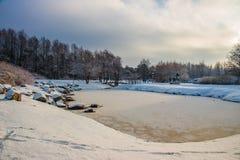 农村的横向 在多雪和冰冷的池塘的美丽的冬天天空 免版税图库摄影