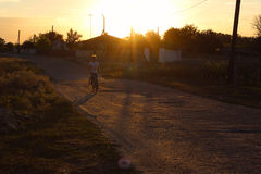 农村风景:一个男孩的剪影一辆自行车的在日落 库存图片